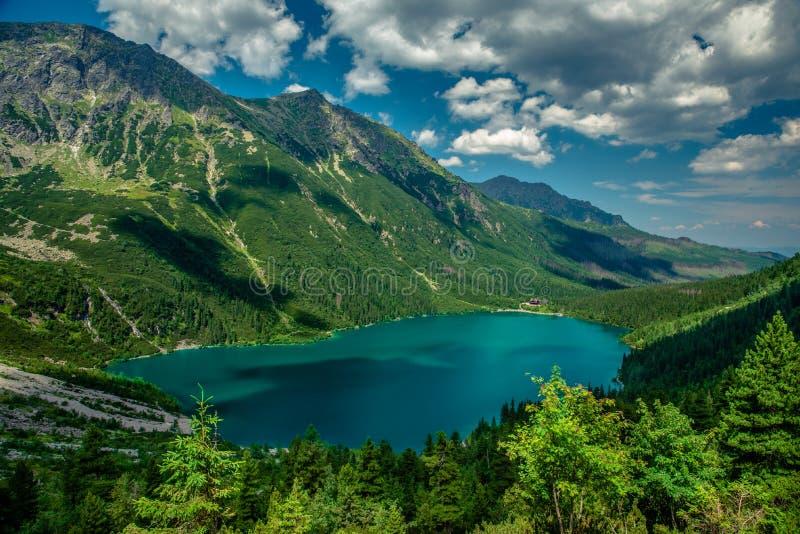 Ansicht über den Türkisfarbsee zwischen den hohen und felsigen Bergen stockfotos