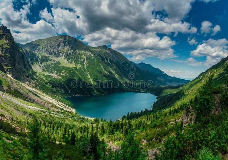 Ansicht über den Türkisfarbsee zwischen den hohen und felsigen Bergen lizenzfreies stockbild