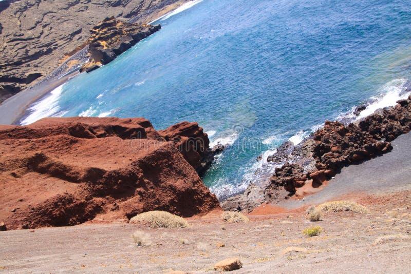 Ansicht über die abgelegene Lagune umgeben durch eindrucksvolle schroffe verwitterte Klippen in den verschiedenen Farben - EL Gol lizenzfreie stockfotos