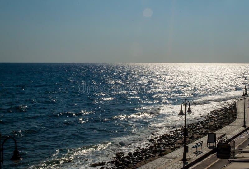 Ansicht über die leere Straße und noch das Meer vom Fenster, früher Abend in der Kleinstadt lizenzfreies stockbild