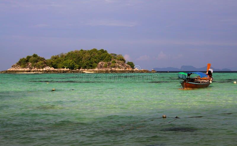 Ansicht über die Türkisbucht, die zum blauen Himmel auf kleiner Insel mit Booten des langen Schwanzes auf Ko Lipe, Thailand kontr lizenzfreies stockbild