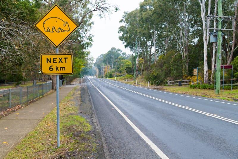 Ansicht über die Verkehrsstraße und gelbes des Wombats Verkehrsschild im Känguru-Tal, ein reizend Dorf, das für seine historische lizenzfreie stockbilder