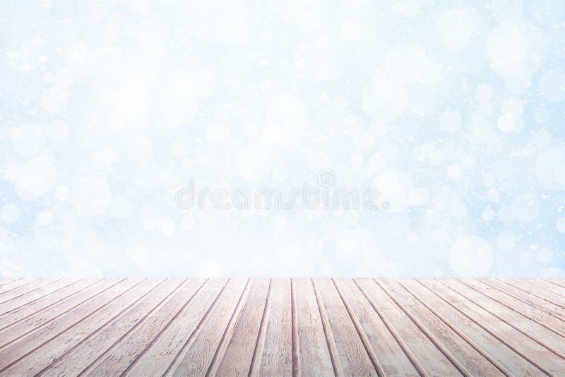 Ansicht über einen braunen Holztisch gegen Schneefälle eines Winters mit bokeh lizenzfreie abbildung