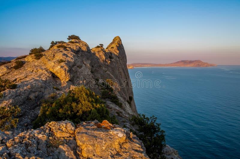 Ansicht über enormen Felsen beleuchtete mit Licht der untergehenden Sonne lizenzfreie stockfotografie