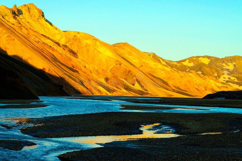 Ansicht über Flussbett mit seichtem Wasser und schwarzem Sand auf orange gelbem glühendem Gebirgszug in der Glättungssonne stockfoto