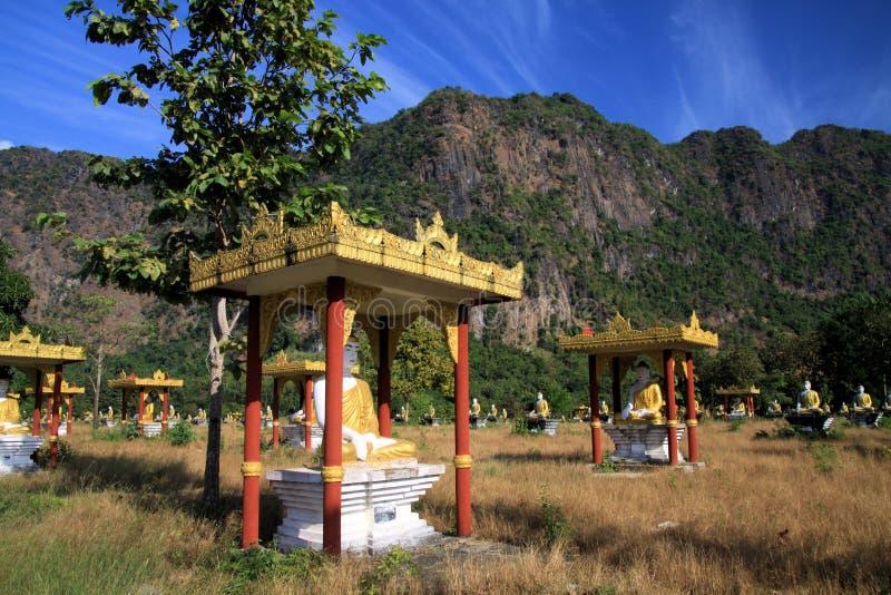 Ansicht über idyllisches abgelegenes Tal mit unzähligen sitzenden Buddha-Statuen gegen Gebirgsgesicht und blauen Himmel lizenzfreie stockbilder