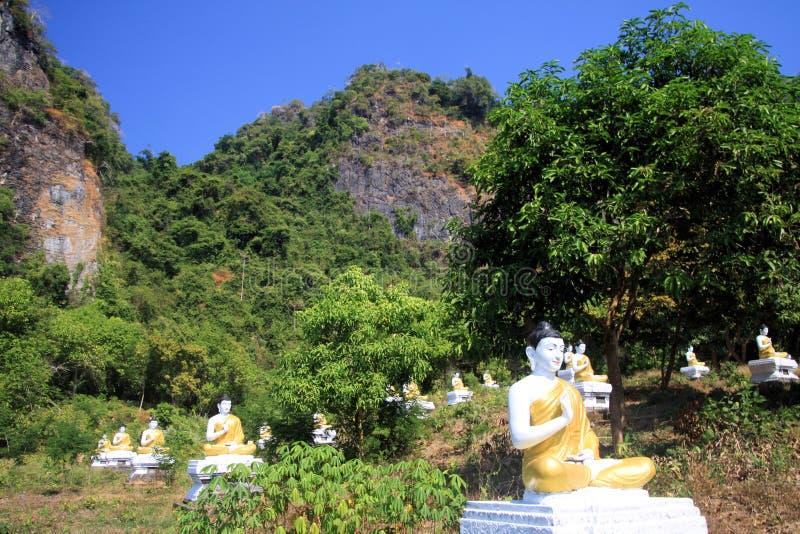 Ansicht über Park mit unzähligen sitzenden Buddha-Statuen in Folge zwischen Bäumen gegen Felsengesicht und blauem Himmel lizenzfreie stockfotografie
