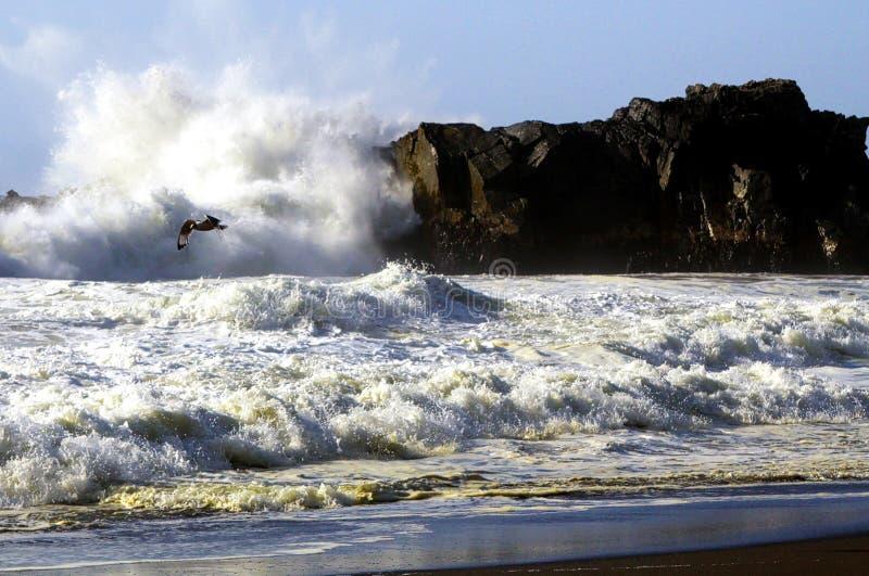 Ansicht über schwarzen Lavasandstrand und weiße wütende schäumende Wasserbrandung auf Welle, die gegen Felsen bricht lizenzfreies stockfoto