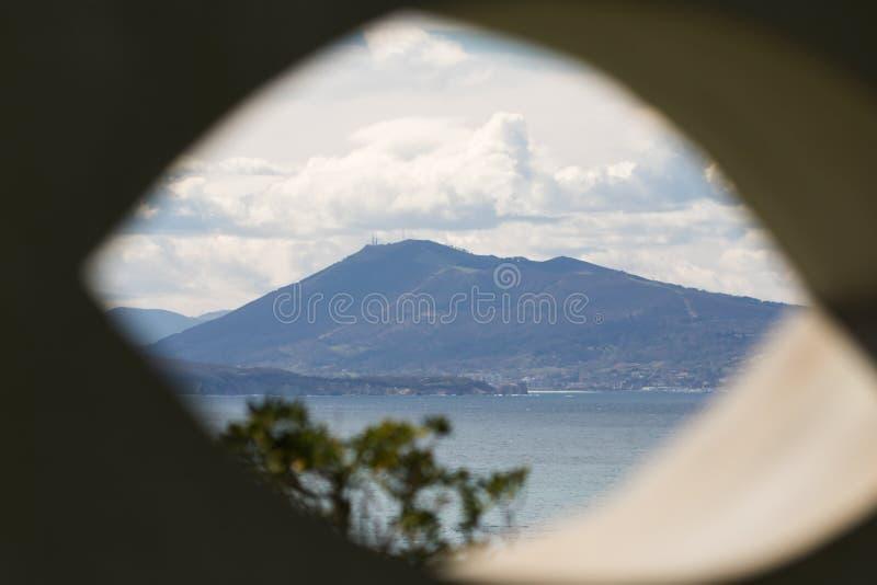 Ansicht über szenisches schönes atlantisches Küstenlinienberg-jaizkibel durch Augenformloch in der Wand stockbild