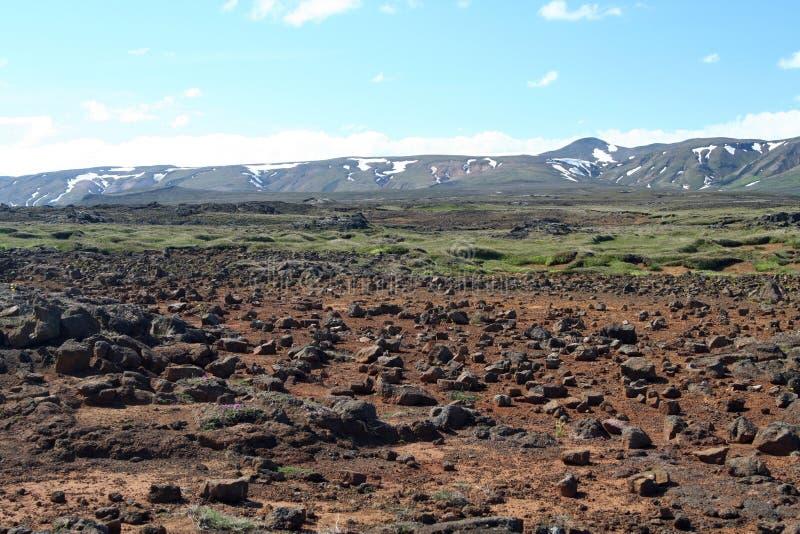 Ansicht über unfruchtbare felsige Ebene auf Gebirgszug mit Stellen des Schnees, Island lizenzfreies stockfoto