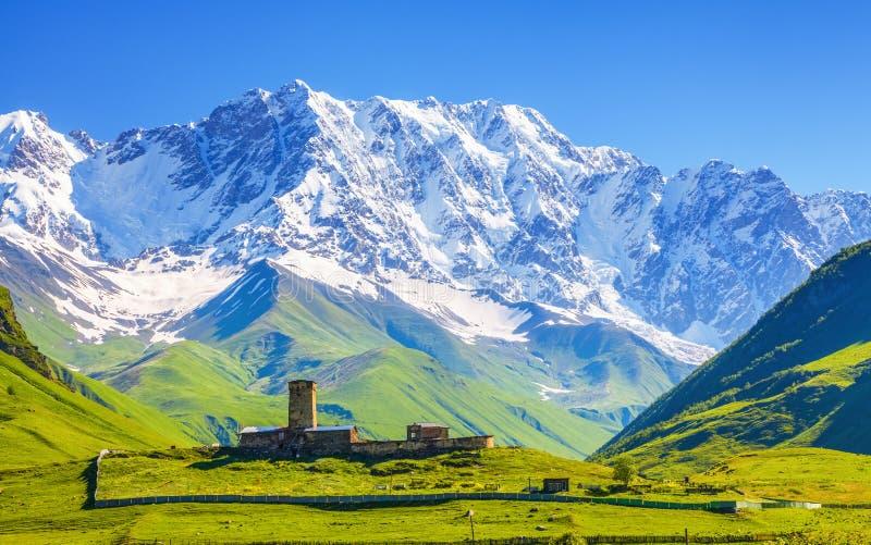 Ansicht über Ushguli-Dorf am Fuß Schnee-mit einer Kappe bedecktem Mt Shkhara stockfoto