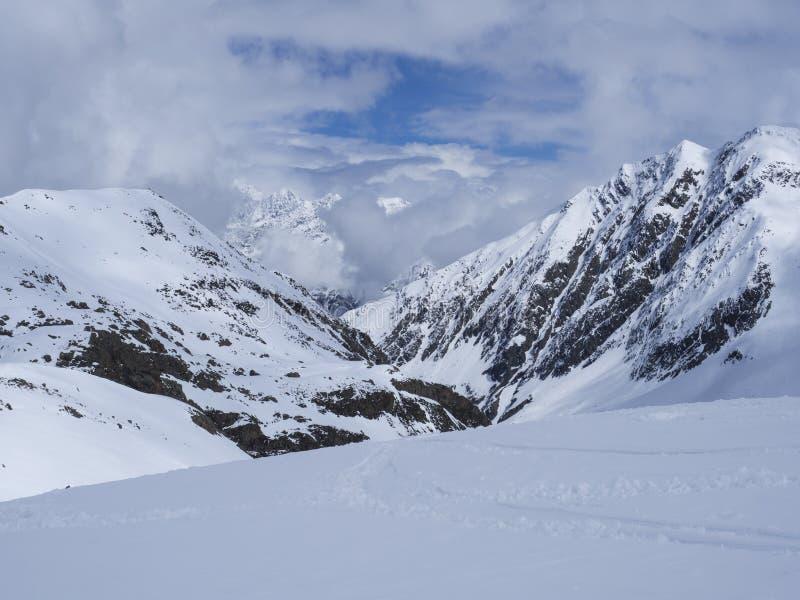 Ansicht über Winterberglandschaft an Skigebiet Stubai Gletscher mit Schnee umfasste Spitzen am sonnigen Tag des Frühlinges Blauer lizenzfreies stockfoto