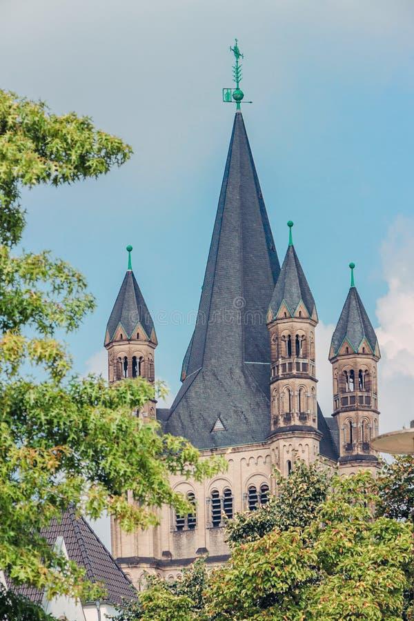 Ansicht auf die Kirche St Martin mit Bäumen an den Rändern in Köln lizenzfreie stockfotografie