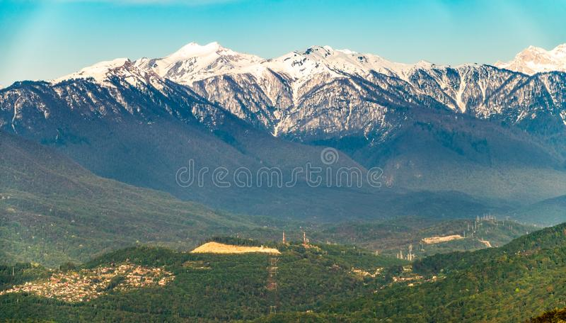 Ansicht bei Sonnenuntergang auf einem grünen hügeligen Tal mit Häusern und hohen schneebedeckten Bergen auf dem Horizont lizenzfreie stockbilder