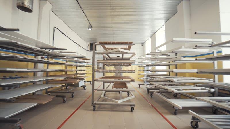 Ansicht der Arbeitskraft im weißen Overall, der den großen Wagen mit hölzernen Brettern auf enormer Werkstatt in der Anlage oder  lizenzfreie stockfotos