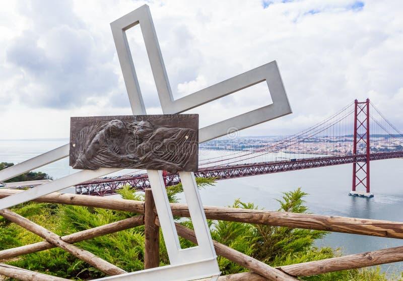 Ansicht der Installation mit einem gefallenen Metallkreuz nahe Christus die Königstatue in Lissabon, Portugal lizenzfreie stockfotografie