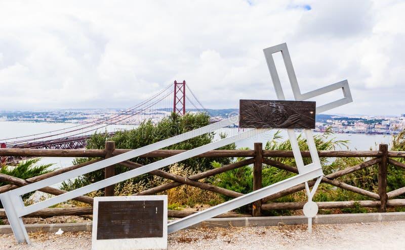 Ansicht der Installation mit einem gefallenen Metallkreuz nahe Christus die Königstatue in Lissabon, Portugal stockbilder