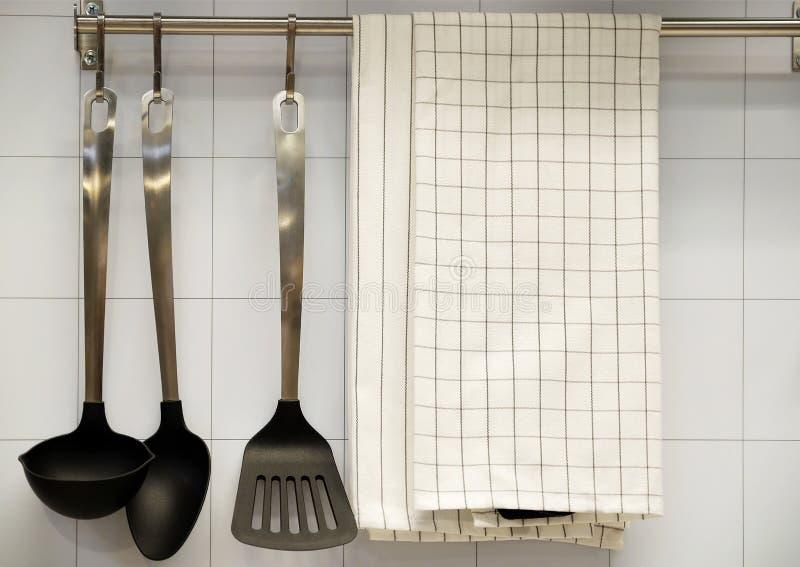 Ansicht der Küchenarbeitsplatte mit einem Schneidebrett, an die Wand einiges nützliches, Eimer und Eimer und Abstreicheisen hänge stockbilder