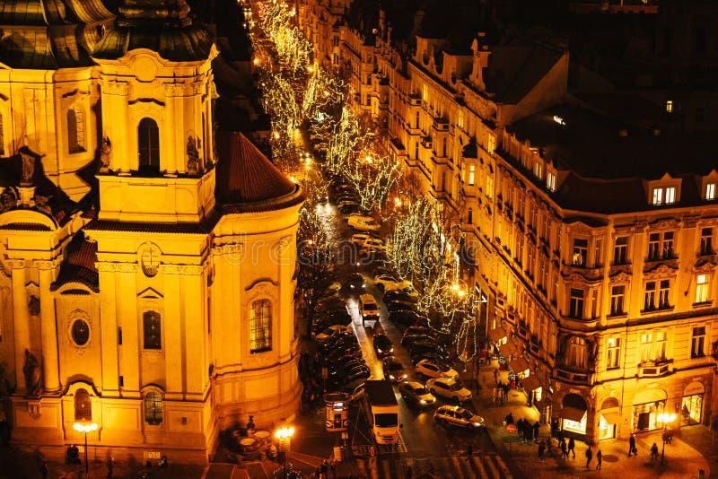Ansicht der Kirche von Sankt Nikolaus und von Straße Nachtweihnachtsdekoration von Prag-` s Hauptplatz Straße, offenes Gebiet lizenzfreie stockbilder