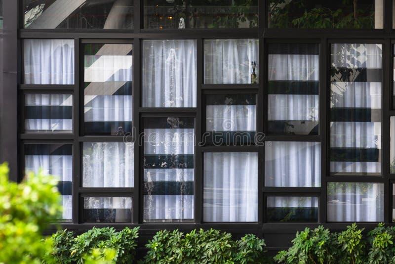 Ansicht der modernen Fenster und des weißen Vorhangs, dessen Glas den gegenüberliegenden Brunnen und den Garten reflektiert Abstr lizenzfreie stockfotos