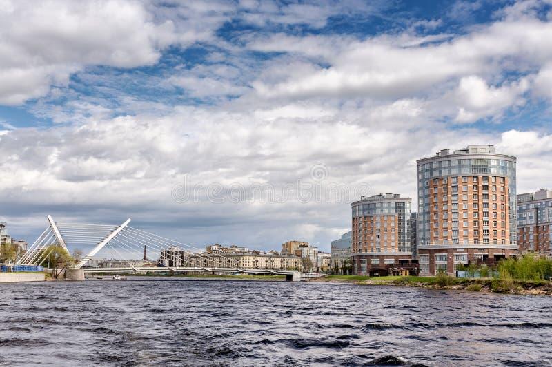 Ansicht der neuen Kabel-gebliebenen Lazarevsky-Brücke und des neuen modernen komplexen Wohnpremiers Palace in St Petersburg lizenzfreie stockbilder