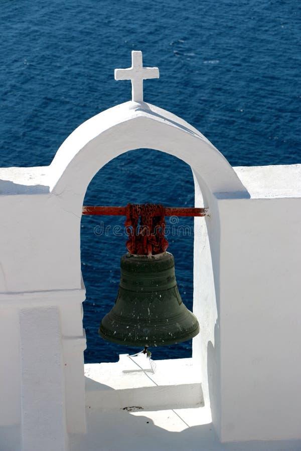 Ansicht der Oberfläche durch traditionellen griechischen weißen Kirchenbogen mit Kreuz und der Glocken in Oia-Dorf von die Kyklad lizenzfreie stockfotografie