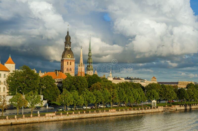 Ansicht der Sonnenuntergang beleuchteten Kathedralenkirche und des St- Peterturms von altem Riga Lettland nach Regen stockfotos