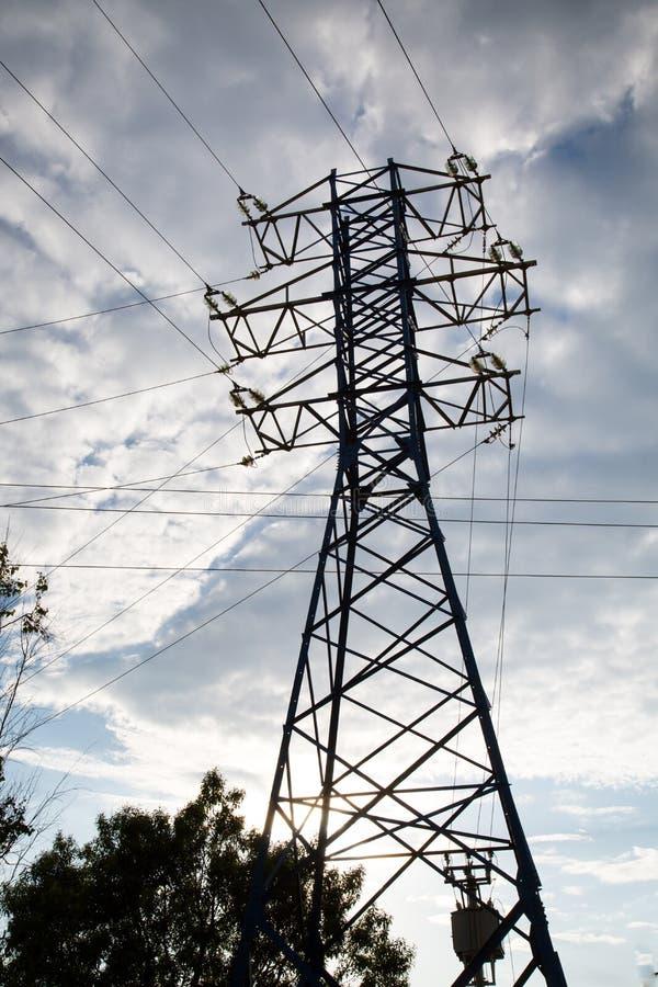 Ansicht der Stromleitung gegen die Wolken des blauen Himmels im Sonnenlicht lizenzfreies stockfoto