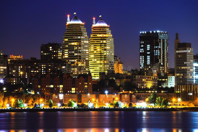 Ansicht der Türme, der Wolkenkratzer und der Gebäude in Dnepr-Stadt nachts, Lichter dachte über den Fluss Dnieper, Ukraine nach lizenzfreie stockbilder