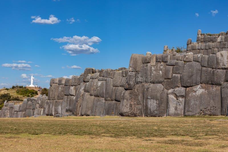 Ansicht der Wand auf dem Sacsayhuaman Inca Archaeological Site und die Statue von Christus nahe Cusco, Peru lizenzfreie stockfotografie