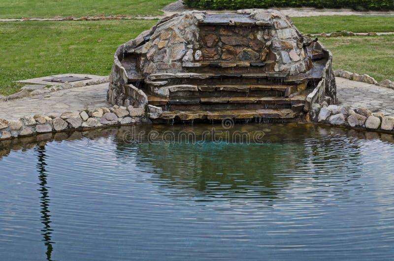 Ansicht des allgemeinen Gartens mit künstlichem Teich der Schönheit und des Kaskadenwasserfalls im Wohnviertel, Stadt Delchevo stockfoto