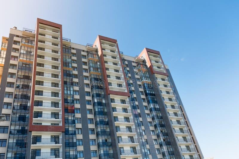 Ansicht des allgemeinen Parks mit eben errichtetem modernem Wohnblock unter blauem Himmel mit wenigen Wolken lizenzfreies stockfoto