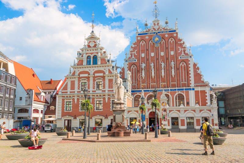 Ansicht des alten Marktplatzes, Roland Statue, die Mitesser bringen nahe St. Peters Cathedral gegen blauen Himmel in Riga, Lettla lizenzfreie stockfotos