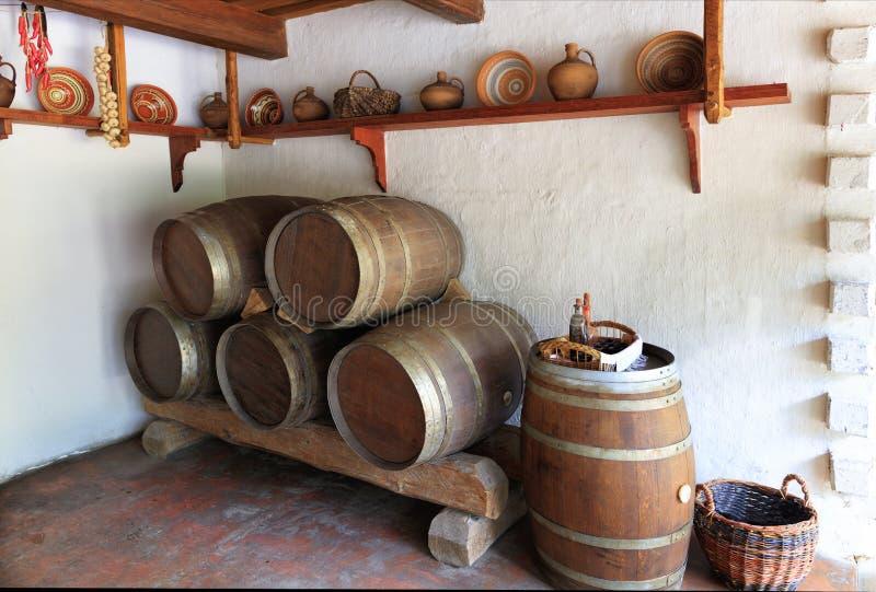 Ansicht des alten Weinraumes des ukrainischen ländlichen Hauses, der Küchengeräte und hölzernen der Eichenfässer lizenzfreies stockbild