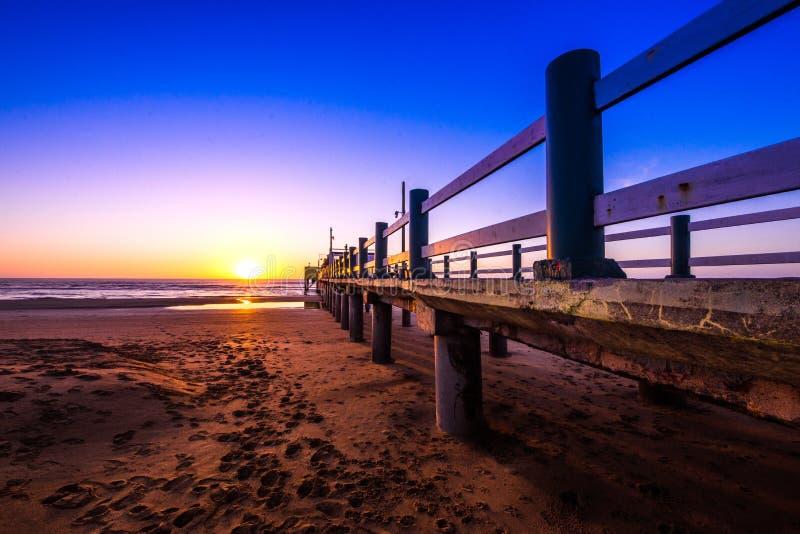 Ansicht des amnecer auf dem Strand vom Pier lizenzfreie stockfotografie