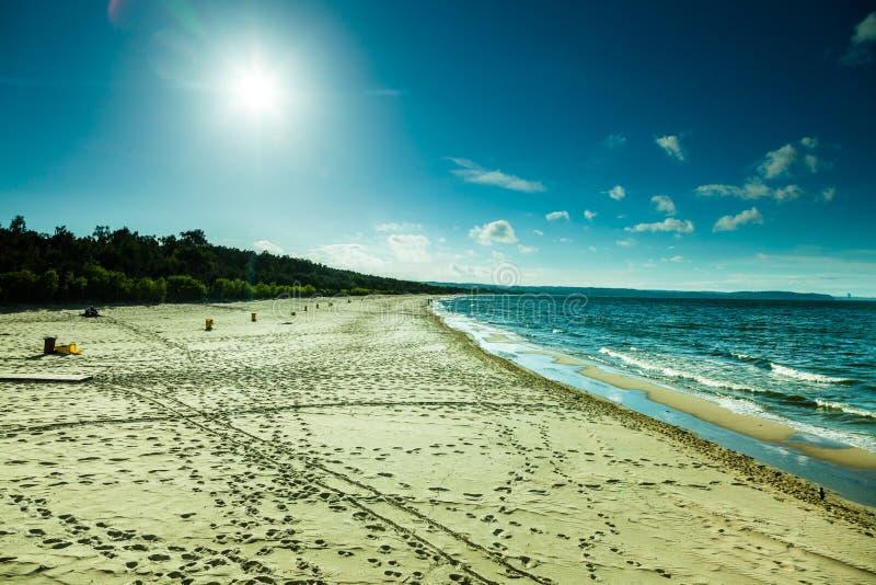 Ansicht des bewölkten Himmels in Meer mit Abdrücken auf einem Strand stockbilder