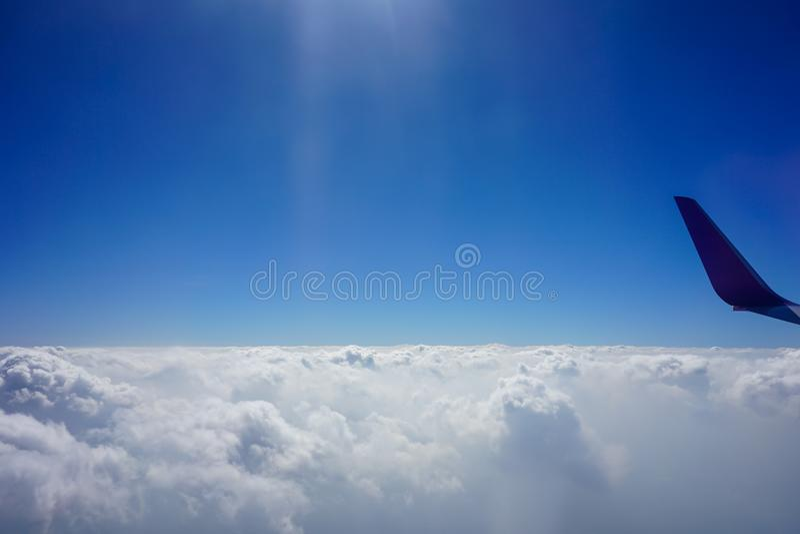 Ansicht des bewölkten Himmels vom Flugzeugfenster lizenzfreie stockfotos