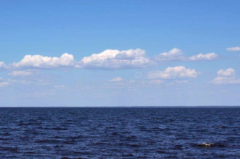 Ansicht des blauen Meeres mit Wolken-, ruhiger und endloseridee stockfotos