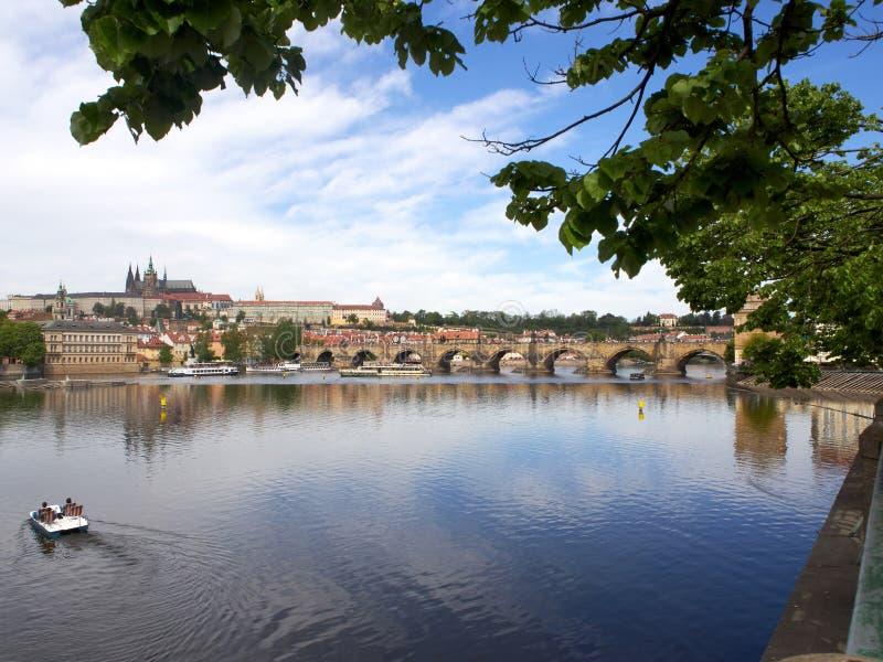 Ansicht des Dammes von die Moldau-Fluss in Prag mit Brücke, Boot und blauem Himmel stockfoto
