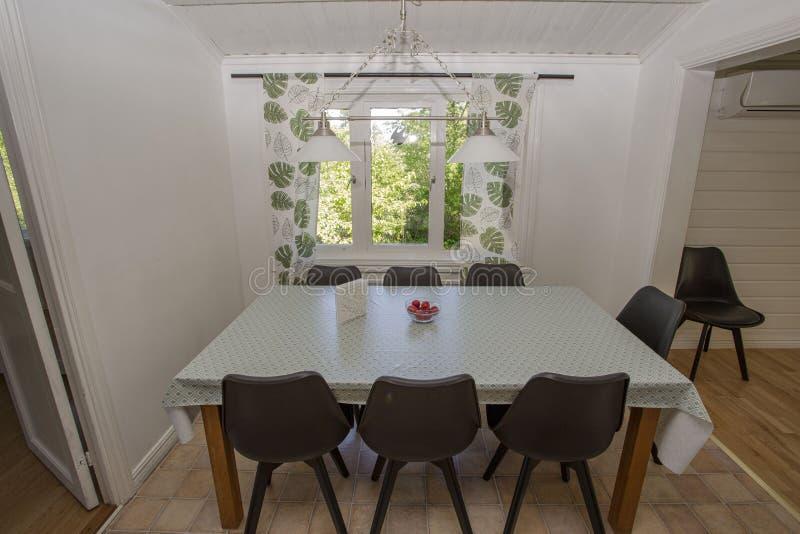 Ansicht des dinning Raumes Weiße Tabelle mit sechs schwarzen Stühlen Skandinavische Art Ttypical des Innenraums stockfotografie