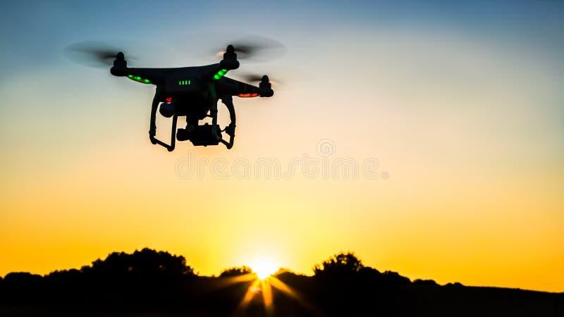 Ansicht des Drohnenfliegens mit Digitalkamera über einem Feld mit Sonnenuntergang stockbild