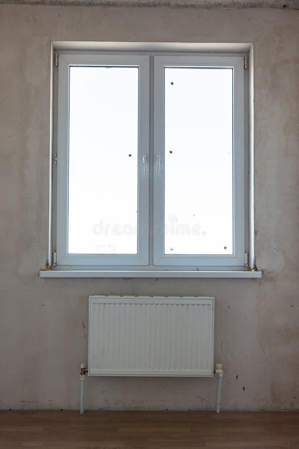 Ansicht des Fensters und des Akkus unter dem Fenster in einem nicht reparierten Raum lizenzfreie stockfotografie