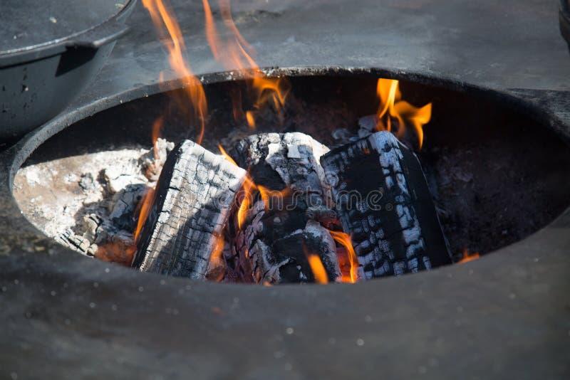 Ansicht des Feuers mit Kohlen im ovalen Loch des Messingarbeiters lizenzfreie stockfotos