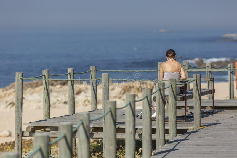 Ansicht des Frauensitzes auf hölzerner Bank im hölzernen Fußgängergehweg, im Strand und im Meer als Hintergrund stockfoto