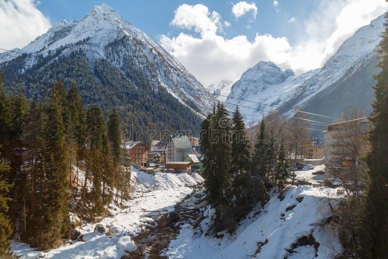 Ansicht des Gebirgsflusses und der Hotels auf dem Hintergrund des Kaukasus am sonnigen Tag des Winters lizenzfreie stockbilder