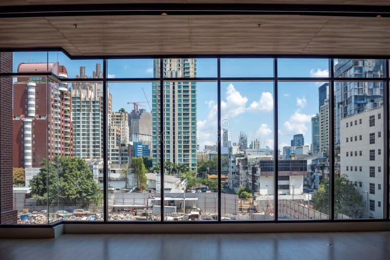 Ansicht des Geschäftsgebiets und des blauen Himmels der Wolken von den großen Glasfenstern im Gebäude lizenzfreies stockbild