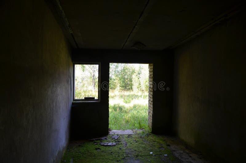 Ansicht des grünen Feldes und der Bäume vom dunklen zerstörten alten Backsteinbau mit einem moosigen Boden durch die Tür und das  lizenzfreie stockfotos