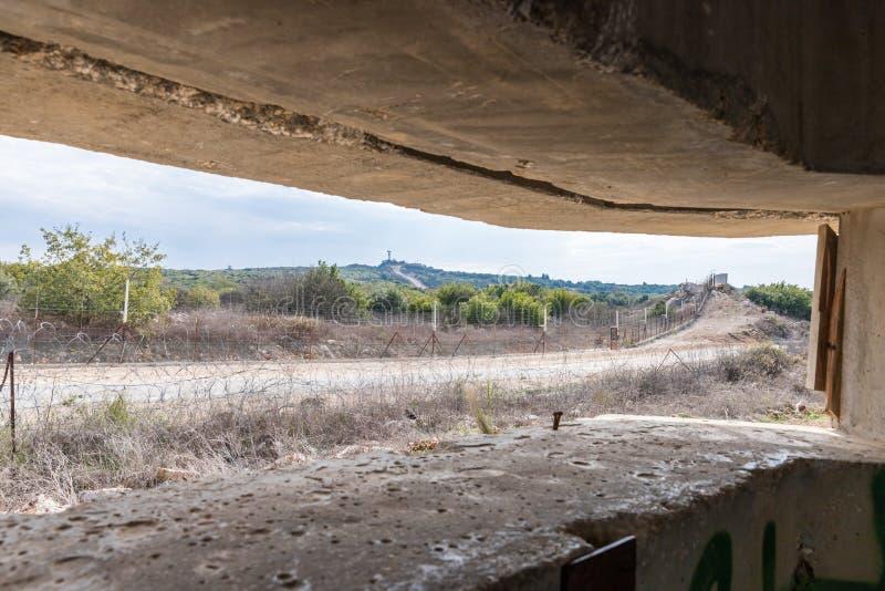 Ansicht des Grenztrennstreifens durch den Embrasure im konkreten Sicherheitstrennungszaun auf der Grenze zwischen Israel und lizenzfreie stockfotos
