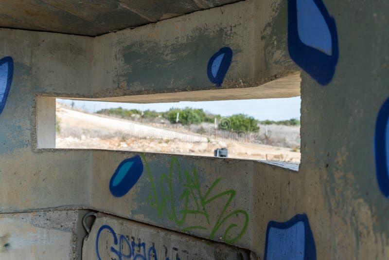 Ansicht des Grenztrennstreifens durch den Embrasure im konkreten Sicherheitstrennungszaun auf der Grenze zwischen Israel und lizenzfreie stockbilder