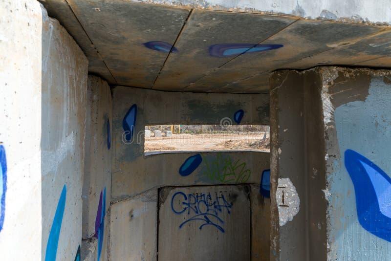 Ansicht des Grenztrennstreifens durch den Embrasure im konkreten Sicherheitstrennungszaun auf der Grenze zwischen Israel und stockfotografie